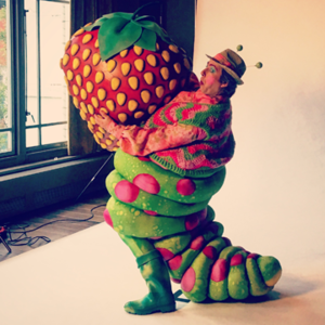 Male in caterpillar costume holding giant strawberry