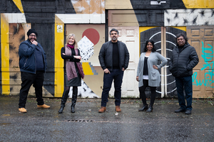 Five people stood in front of street art